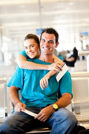 happy young couple waiting for their flight at airport photo