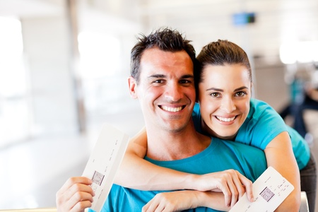 happy young couple at airport with boarding pass photo