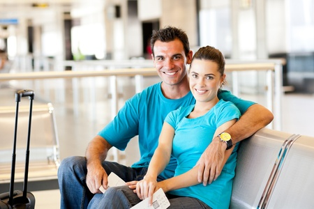 casual young couple waiting for flight at airport photo