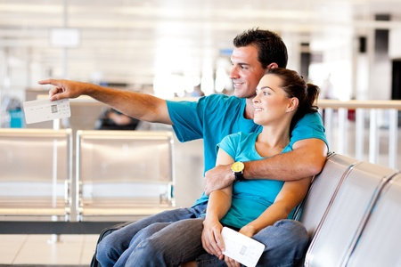 young woman sitting: casual young couple waiting for flight at airport