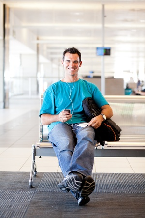 casual young man waiting for flight at airport photo