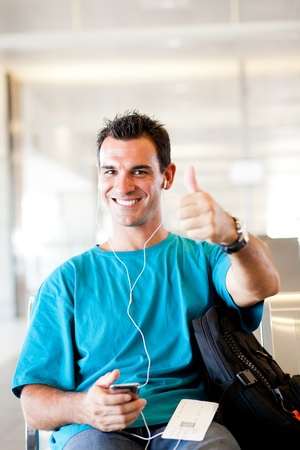 happy young traveller giving thumb up at airport photo
