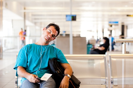 tired young male traveller sleeping in airport Stock Photo - 12897872