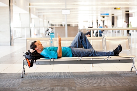 young man lying on airport chairs and resting photo