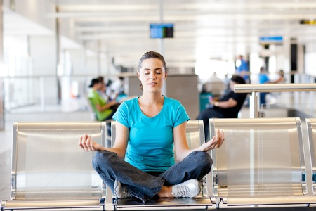 donna seduta sedia: giovane e bella donna casuale facendo meditazione yoga presso l'aeroporto