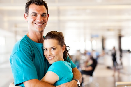 happy young couple hugging at airport photo
