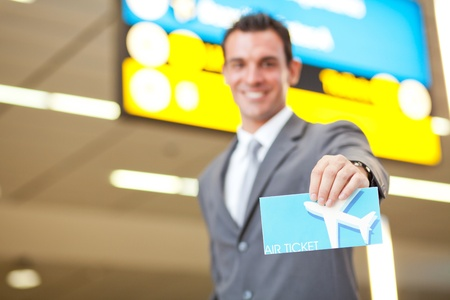 happy young businessman presenting air ticket, focus on foreground photo