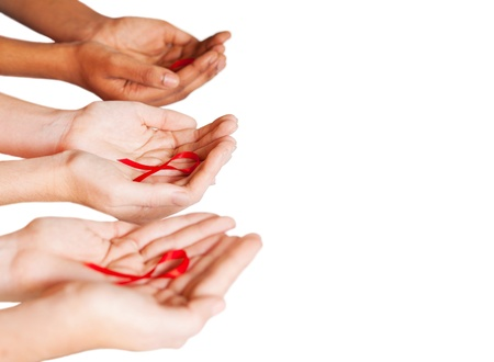 diverse hands: hands holding red ribbon to rise AIDS HIV awareness