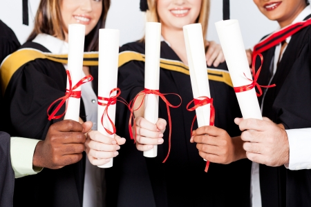 group of multiracial graduates holding certificates photo