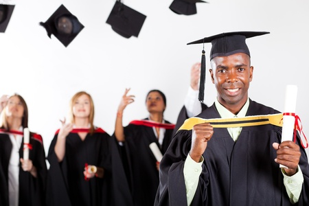 academic robe: happy african graduate at graduation with classmates in background