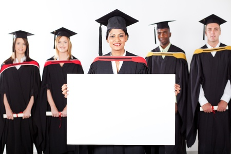 female indian graduate holding white board with classmates in background photo