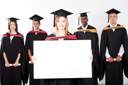 graduates: pretty female graduate holding white board with classmates in background Stock Photo