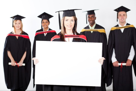 attractive graduate holding white board with classmates in background photo
