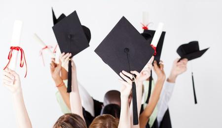 academic achievement: graduate holding graduation caps and certificate