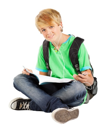 teen boy sitting on floor reading book isolated on white photo
