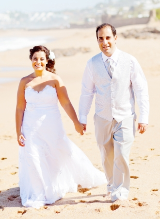 groom and bride holding hands walking on beach photo