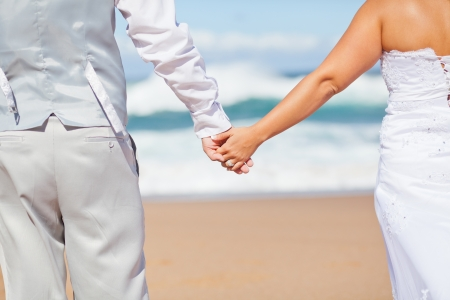 rear view of groom and bride holding hands on beach Stock Photo - 13737481