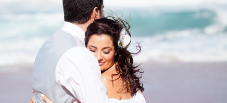 loving bride and groom hugging on beach photo