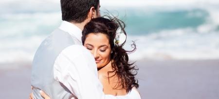 loving bride and groom hugging on beach photo