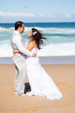 happy groom and bride hugging on beach photo