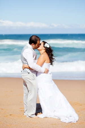 newlywed couple kissing on beach photo