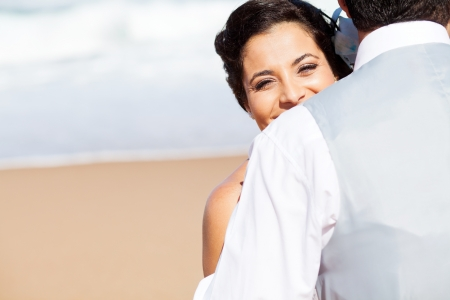 happy young woman hugging husband on beach photo