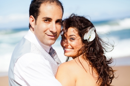 happy groom and bride on beach photo