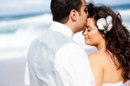 loving groom kissing brides forehead on beach photo