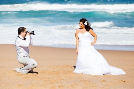 groom taking brides photos on beach photo