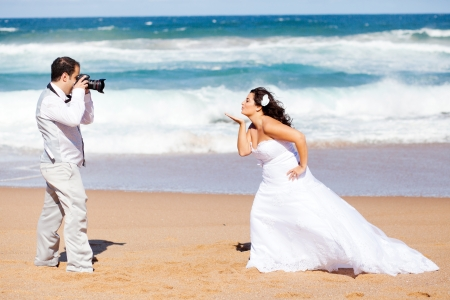 beach kiss: wedding photo shoot - groom taking brides photo Stock Photo