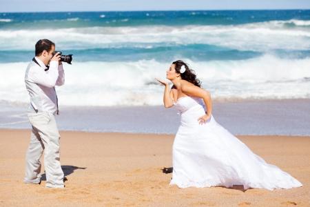 beach wedding: wedding photo shoot - groom taking brides photo Stock Photo