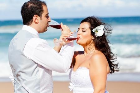 newlywed couple drinking champagne on beach photo