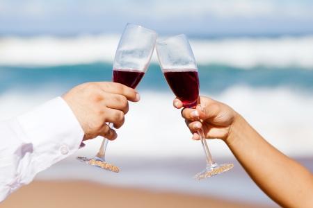 brindisi spumante: l'uomo e la donna bevendo champagne sulla spiaggia Archivio Fotografico