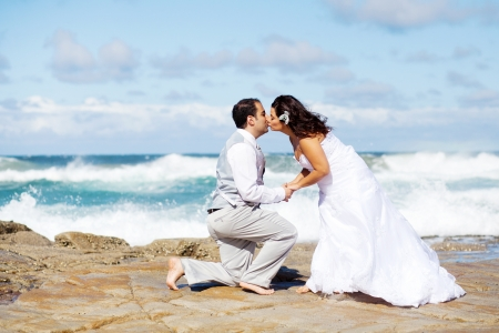 groom and bride kissing on beach rocks Stock Photo - 13737452