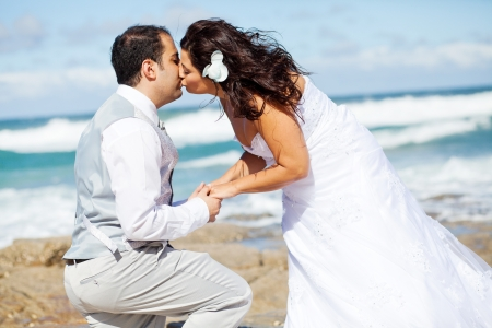 newlywed couple kissing on beach rocks photo