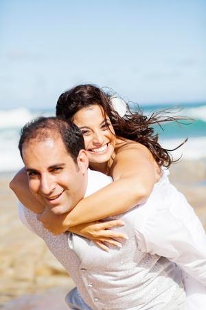 piggy back: happy groom and bride piggyback on beach  Stock Photo