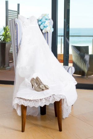 bridal dress, bouquet and shoes on a chair photo