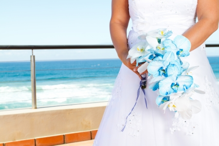 bride holding beautiful bouquet, background is sea view photo
