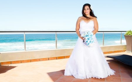 beautiful bride with bouquet and sea view photo
