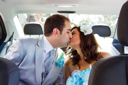 Newlywed couple kissing each other in limousine photo