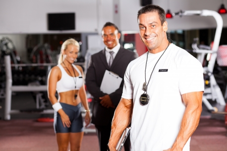 handsome male gym personal trainer in front of colleagues photo