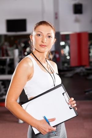 personal trainer woman: female personal trainer inside gym Stock Photo