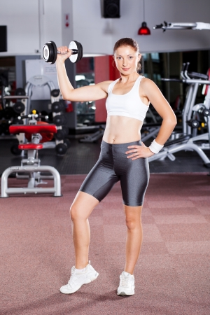fitness woman working out with dumbbell in gym photo