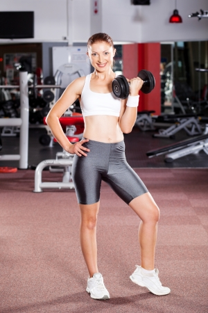 young fitness woman using dumbbell in gym photo