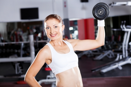 young fitness woman exercising with dumbbell in gym photo