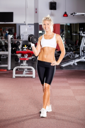 young fitness woman doing workout with dumbbell photo