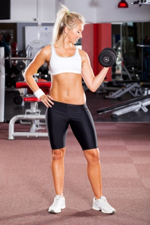 young woman doing workout with dumbbell in gym photo