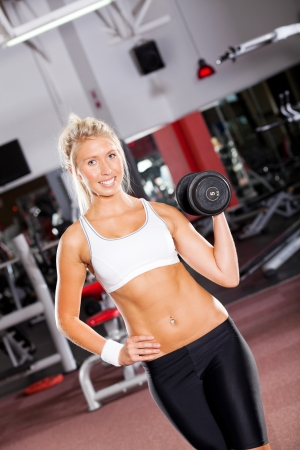 young fitness woman with dumbbell in gym Stock Photo - 13738433