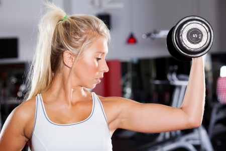 young fitness woman exercising with dumbbell Stock Photo - 13738532
