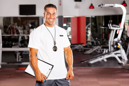 handsome male personal trainer in gym photo